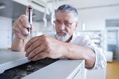 senior male researcher carrying out scientific research in a lab using a gas chromatograph (shallow