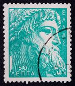A Greek Stamp Showing The Bearded Face Of A Statue Of A Man