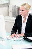 Blonde woman working at a desktop computer