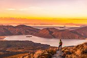 Hiking wanderlust adventure man hiker alone looking at sunset nature landscape of mountains and lake poster