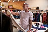 Young black man looking at clothes in clothes shop poster