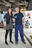 Portrait of young mechanic standing with female customer in auto repair shop