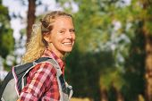 Hiking blonde woman healthy and active walking with backpack smiling happy in forest. Female hiker b poster
