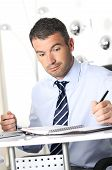 stock photo of profusion  - busy man hiding behind a stack of files - JPG