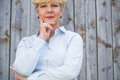Portrait of an active senior woman looking at camera with a serene and pensive facial expression whi poster