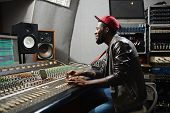 Happy young rapper sitting by recording equipment in audio production studio poster