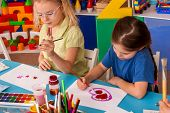 Small students painting in art school class. Child drawing by paints on table. Children study Valent poster