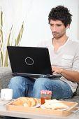 Man having breakfast whilst using laptop