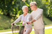 old age, people and lifestyle concept - happy senior couple with fixie bicycle talking at summer cit poster