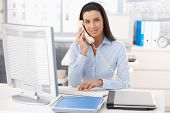 Portrait of smiling woman working in office, using computer and landline phone.?