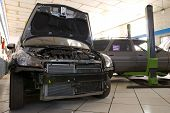 pic of car repair shop  - Low profile front shot of a black modern car with hood open - JPG