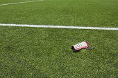 Artificial grass field background with leg protection pad in the foreground