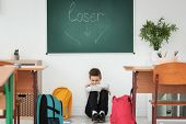 Little boy sitting under chalkboard with word Loser indoors. Bullying in school poster