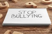 Notebook with text Stop bullying on wooden background, closeup poster