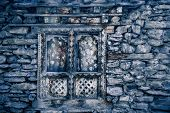 Ancient stone wall with the stylish window with wood carving. Perfect vintage background in blue tin poster