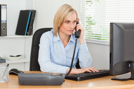 picture of blonde woman  - Smiling businesswoman on the phone looking at her screen in her office - JPG