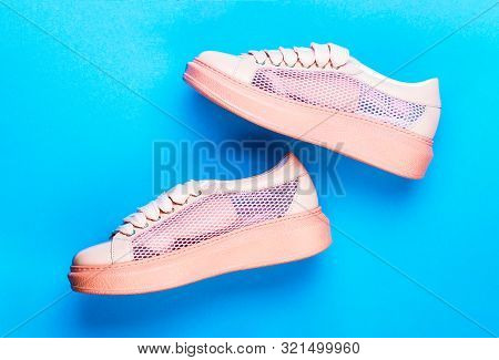 poster of Sneakers Isolated On Blue Background, Fashion. Sport Shoes. Pair Of Pink Sport Shoes On Blue Backgro