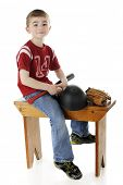 picture of straddling  - A young elementary boy happily straddling a locker room bench with his bat - JPG