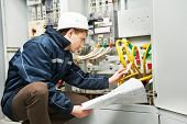 stock photo of inspection  - Electrician builder at work inspecting cabling connection of high voltage power electric line in industrial distribution fuseboard - JPG