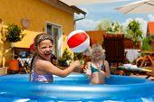 Kinder sind sie Schwestern spielen im Wasser mit einem Ball in den Garten vor dem Haus