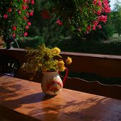 A Vase  In Open Veranda, With Yellow Flowers On A Table, Outdoor Shot poster