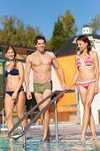 zwei glückliche junge Frauen und ein Mann Freunde zu Fuß in das Wasser eines Schwimmbades; Sie sind Verschleiß