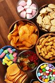 Salty Snacks. Pretzels, Chips, Crackers And Candy Sweets On Table poster