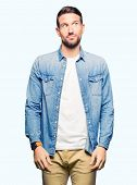 Handsome man with blue eyes and beard wearing denim jacket smiling looking side and staring away thi poster