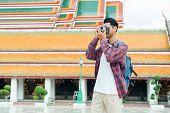 Asian Man Tourist Walk Taking Photo With Film Camera  At Wat Suthat Thepwararam Ratchaworawihan Bang poster