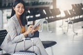 Business Women Sit And Wait At Passenger Boarding Terminal In Airport,luggage And Suicase Bag On The poster