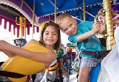 stock photo of merry-go-round  - Kids having fun on a carnival Carousel - JPG