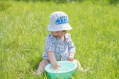 Child Plays With A Basin Of Water On The Grass. Funny Baby Boy Playing Outside With Water And Bubble poster