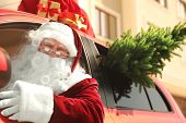 Authentic Santa Claus With Fir Tree And Bag Full Of Presents On Roof Driving Modern Car, Outdoors poster