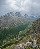 A High Alpine Mountain Valley And River. The River Passes Through High Mountain Peaks And Rough Alpi poster