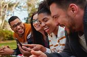 Group Of Multi Ethnic Friends In College Lying Together In The Park Enjoying Watching Text Or Video  poster