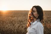 Young Girl In Wheat Field At Sunset. Curly-haired Brunette White Caucasian Girl Watching The Sunset  poster