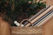 Rustic Basket With Fir Branches,festive Wrapping Paper, Cozy Gloves On Rustic Wooden Background. Fla poster