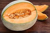 stock photo of muskmelon  - One partially cut cantaloupe macro with slices to the back and side - JPG