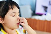 Asian Little Girl Sick With Hand Holding The Nose Get Cold And Blow Nose The Flu Season / Child Runn poster