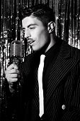 Attractive Latino Man Singing In Front Of Vintage Microphone In Nightclub With Silver Curtain In Bac poster