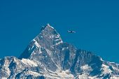 a airplane passing by the snow mountain