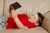 picture of couch potato  - Couch potato concept of boy playing video game while resting on sofa - JPG