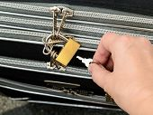 Woman Hand Holding The Key And Going To Unlock The Padlock On A Travel Suitcase Zippers. Protect The poster