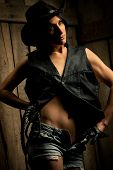Beautiful sexy woman with  Black Leather Flogging Whip in cowboy hat and Shorts against wooden backg