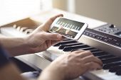 Piano Lesson Online. Man Watching Video Tutorial With Mobile Phone And Practising Playing. Person Le poster