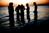 stock photo of baptism  - six young men in ocean water during sunset - JPG