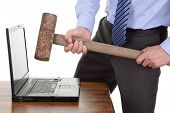 Businessman with a sledgehammer ready to smash his laptop computer concept for frustration, failure