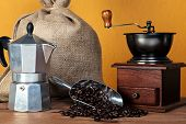 Still life photo of a  caffettiera or moka pot with traditional coffee grinder hessian sack and arab