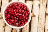 Small bowl filled with ruby red antioxidant pomegranate seeds