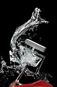 picture of high heels  - High heel shoe breaking a perfume bottle with a large splash of liquid isolated on a black background - JPG